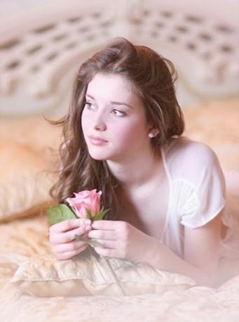 Image d'une jeunne femme avec des fleurs sur un lit